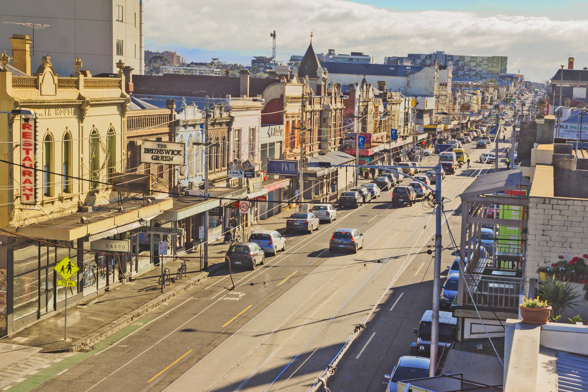 Aerial view of a long straight street of shops and traffic, Sydney Street, Brunswick, Melbourne