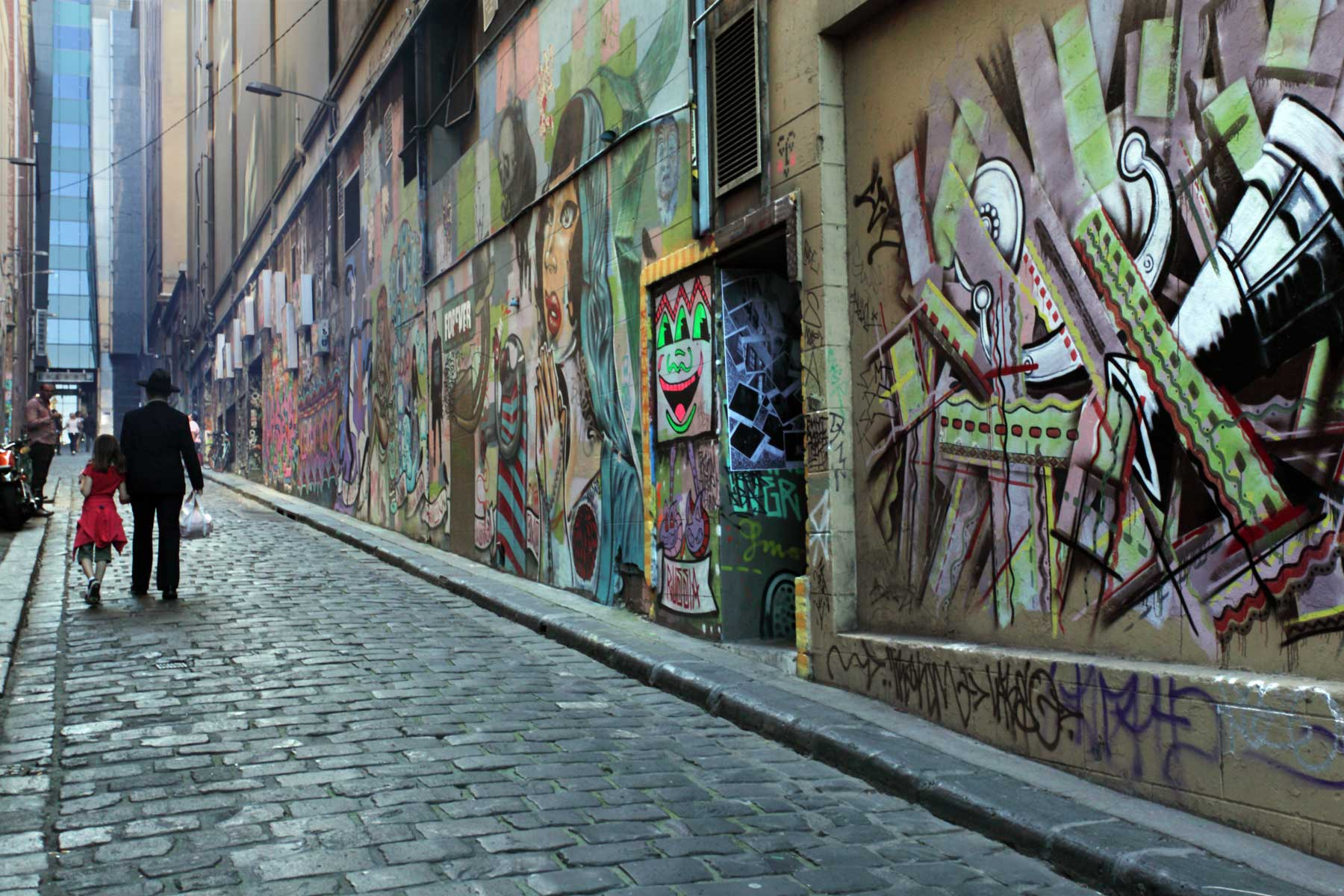 A man and young girl walk down a cobblestoned lane with graffiti on the walls, Melbourne
