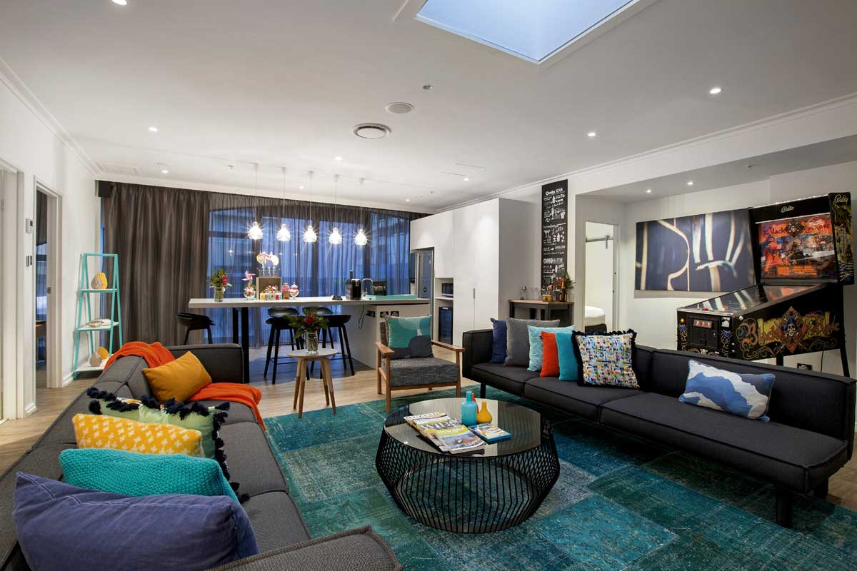 View of a hotel penthouse lounge with colourful cushions and throws on the couches, Ovolo, Melbourne