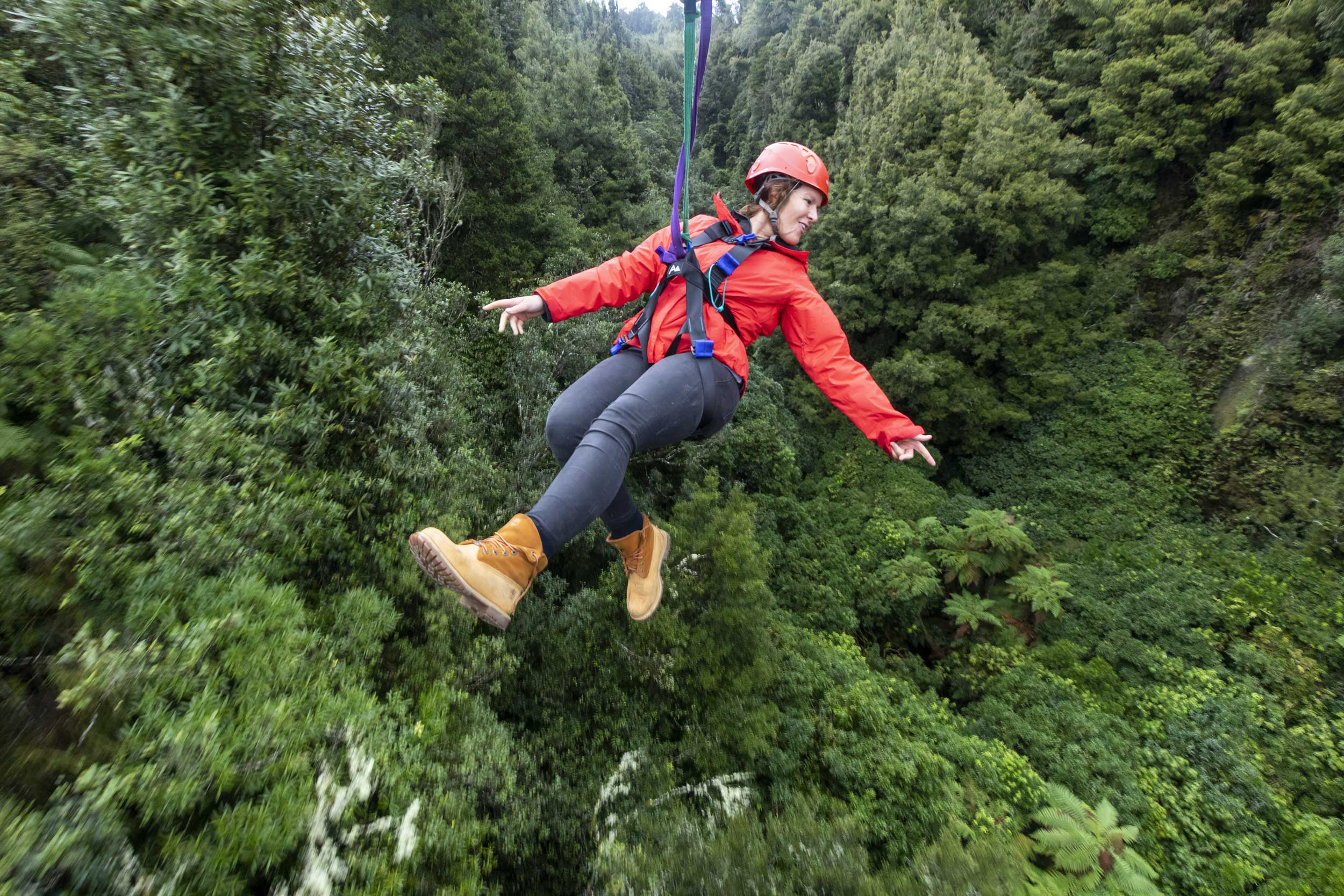 Woman ziplining backwards high above treetops, Rotorua