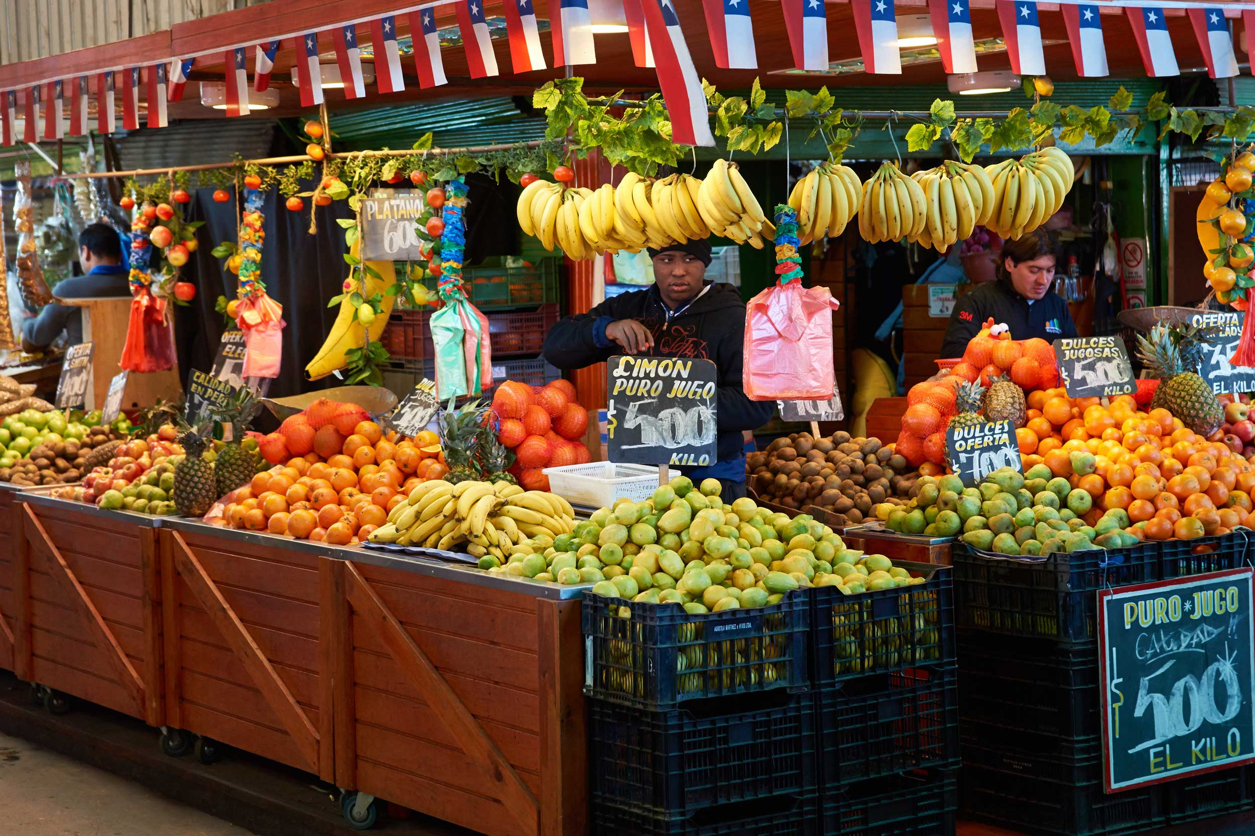 Vendors at a fruit stall piled high with fruit, Santiago Chile