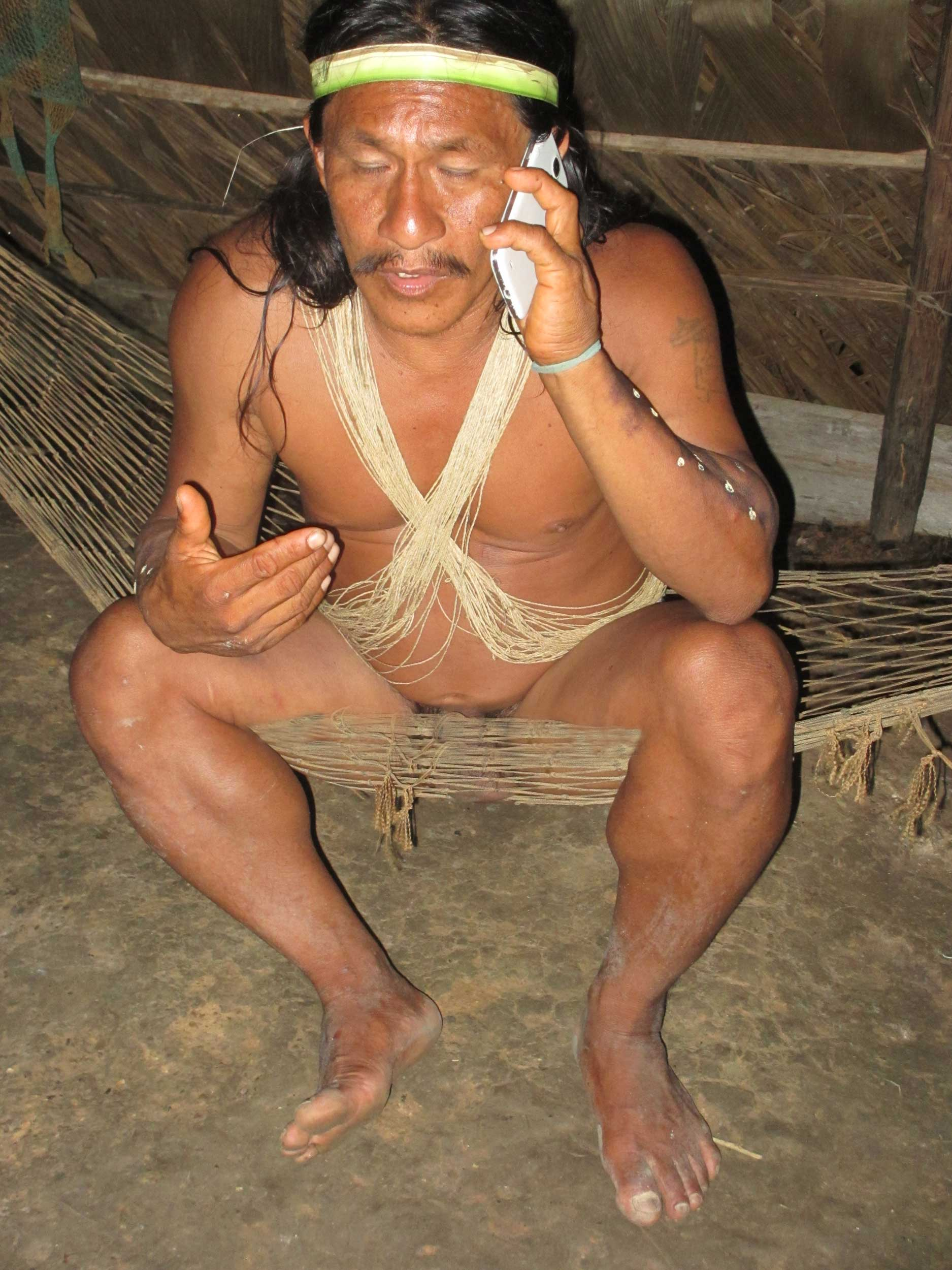 Naked man sitting in a hammock talking on a mobile phone, Bameno, Ecuador