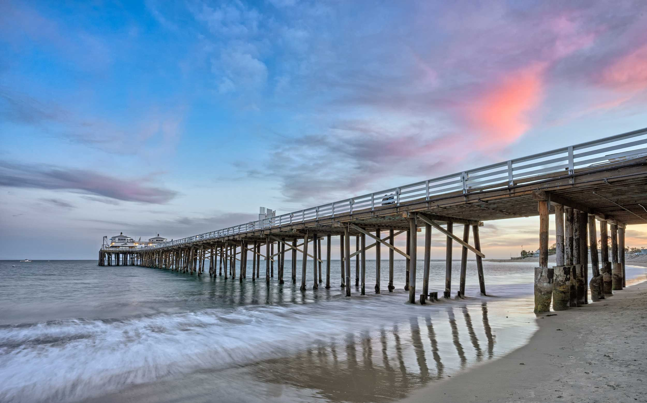 A long pier on wooden stilts extending out to sea at Malibu