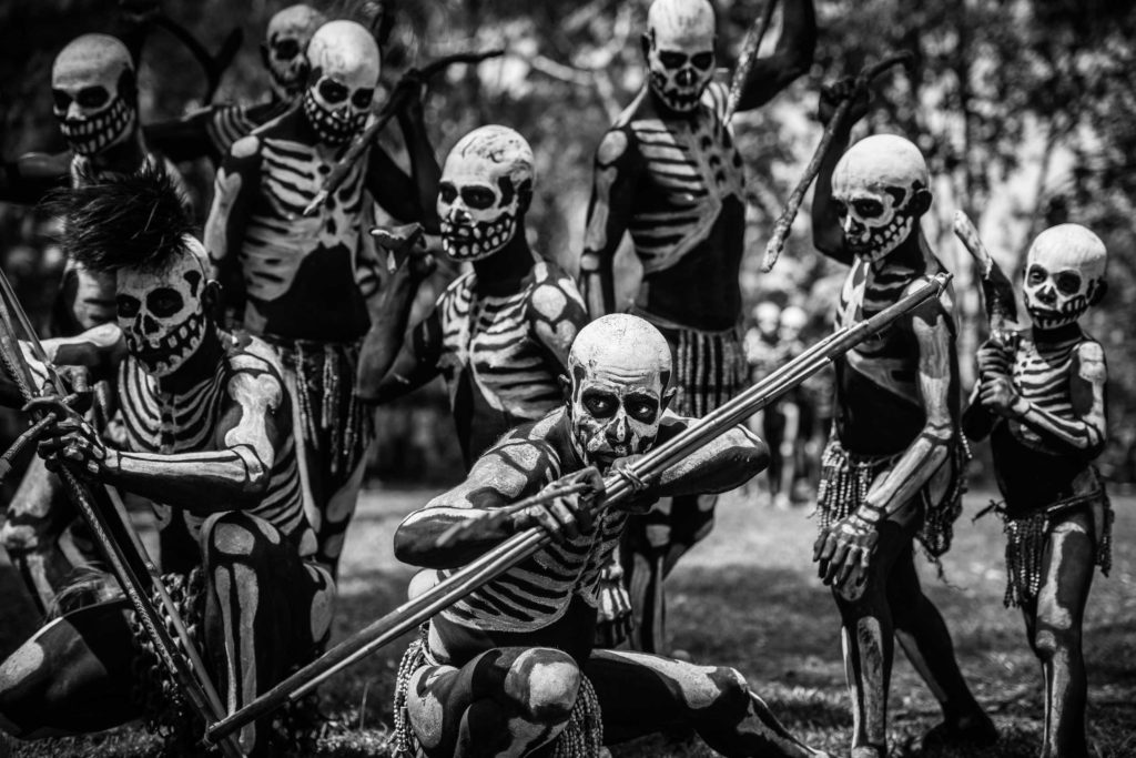 Skeleton Spirit Dancers from Chimbu (also spelt Simbu) province. The Chimbu tribes' impressive bilas, or body ornamentation, originated as a way to intimidate their enemies. Here a group of young men, painted in black and white to simulate skeletons, leap forward and mock-threaten onlookers with bows, arrows, war-like cries and whooping sounds.