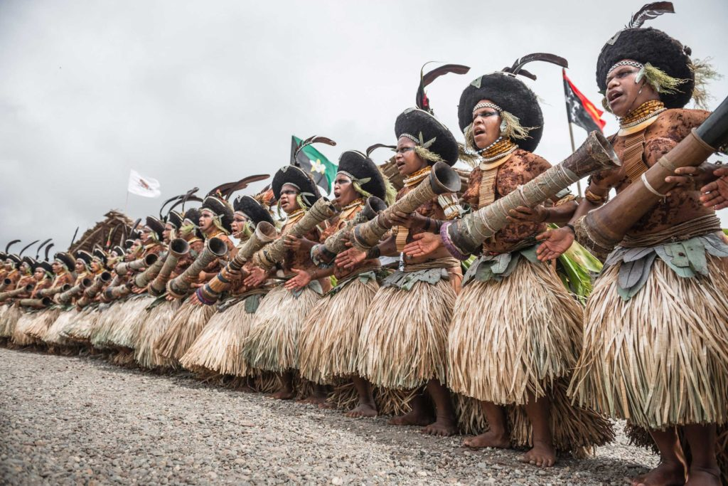 Famous Suli Muli dancers with clay-painted bodies and giant round hats, the trademark of Enga province. Their dances are unique in the country. Forming an aesthetic spear line, they rhythmically jump up and down in unison to the beat of the kundu — traditional PNG drums.