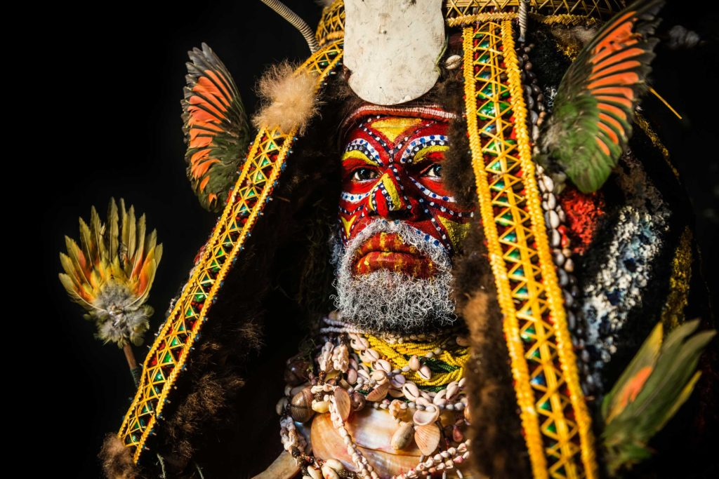 Tambul man in full traditional bilas, or body ornament. The Tambul tribe live at the foot of the second highest mountain in Papua New Guinea, Mt. Giluwe. For special occasions, the men wear elaborate and brightly-coloured headdresses decorated with birds' feathers, and paint their faces in red and yellow stripes making them look frightening. Despite some cultural similarities from sharing the borders of Western Highlands, Enga and Southern Highland Provinces, Tambul traditional attire and body paint are very unique.