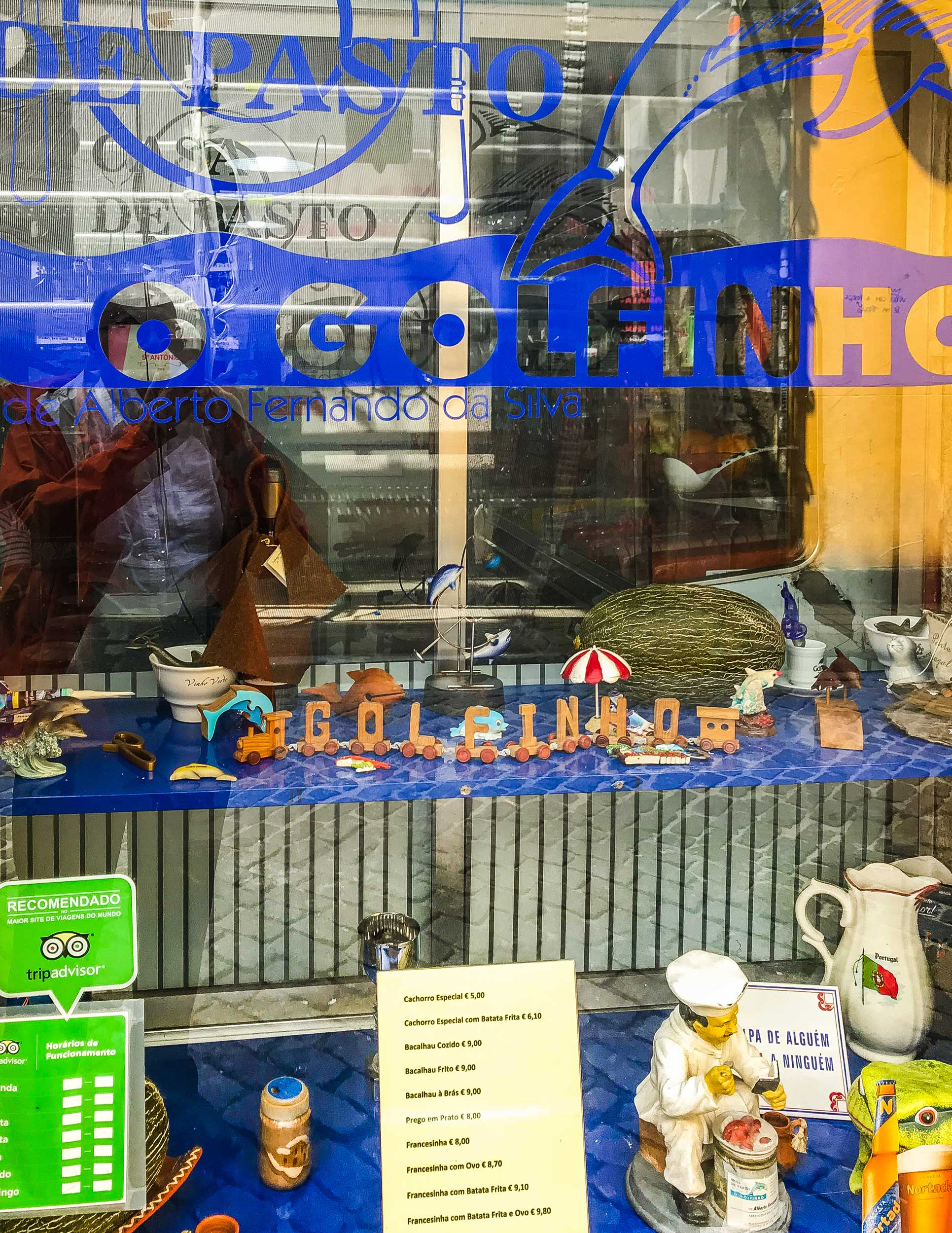 Looking through a glass shop window with with little artefacts on the window ledge, Porto