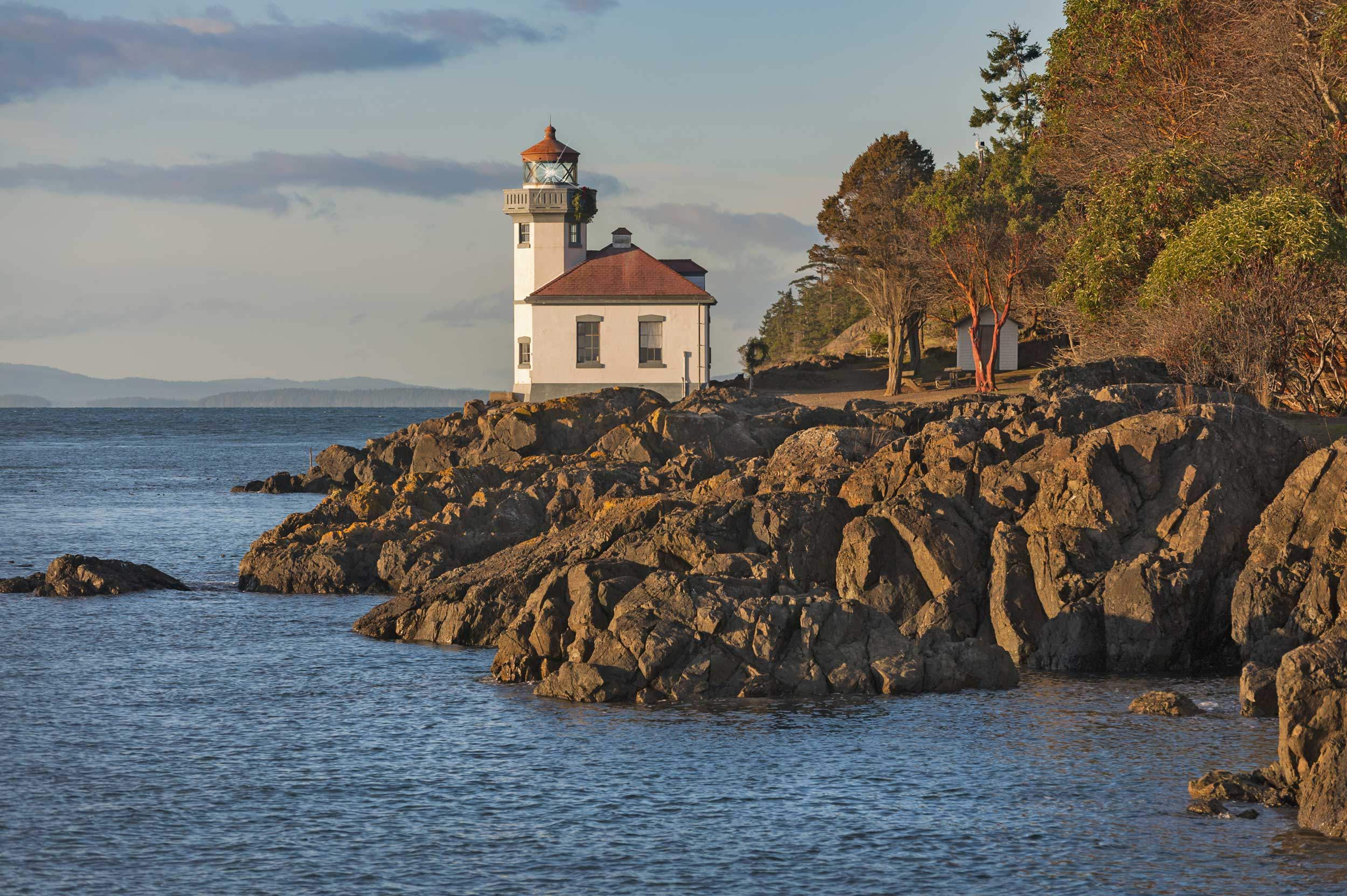 A lighthouse building set on a rocky point with trees