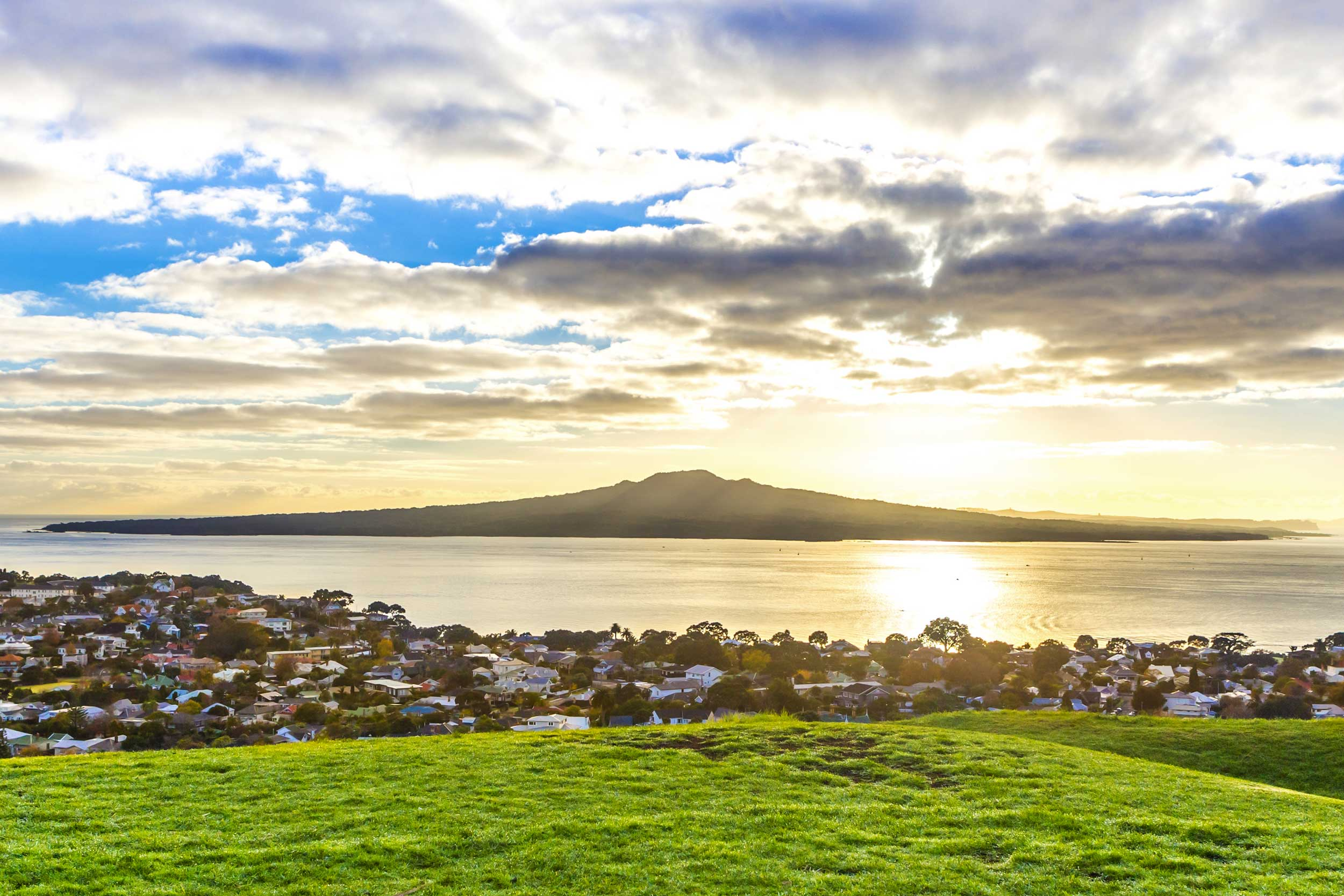 A volcanic cone rising out of the sea in the distance seen from Auckland city.