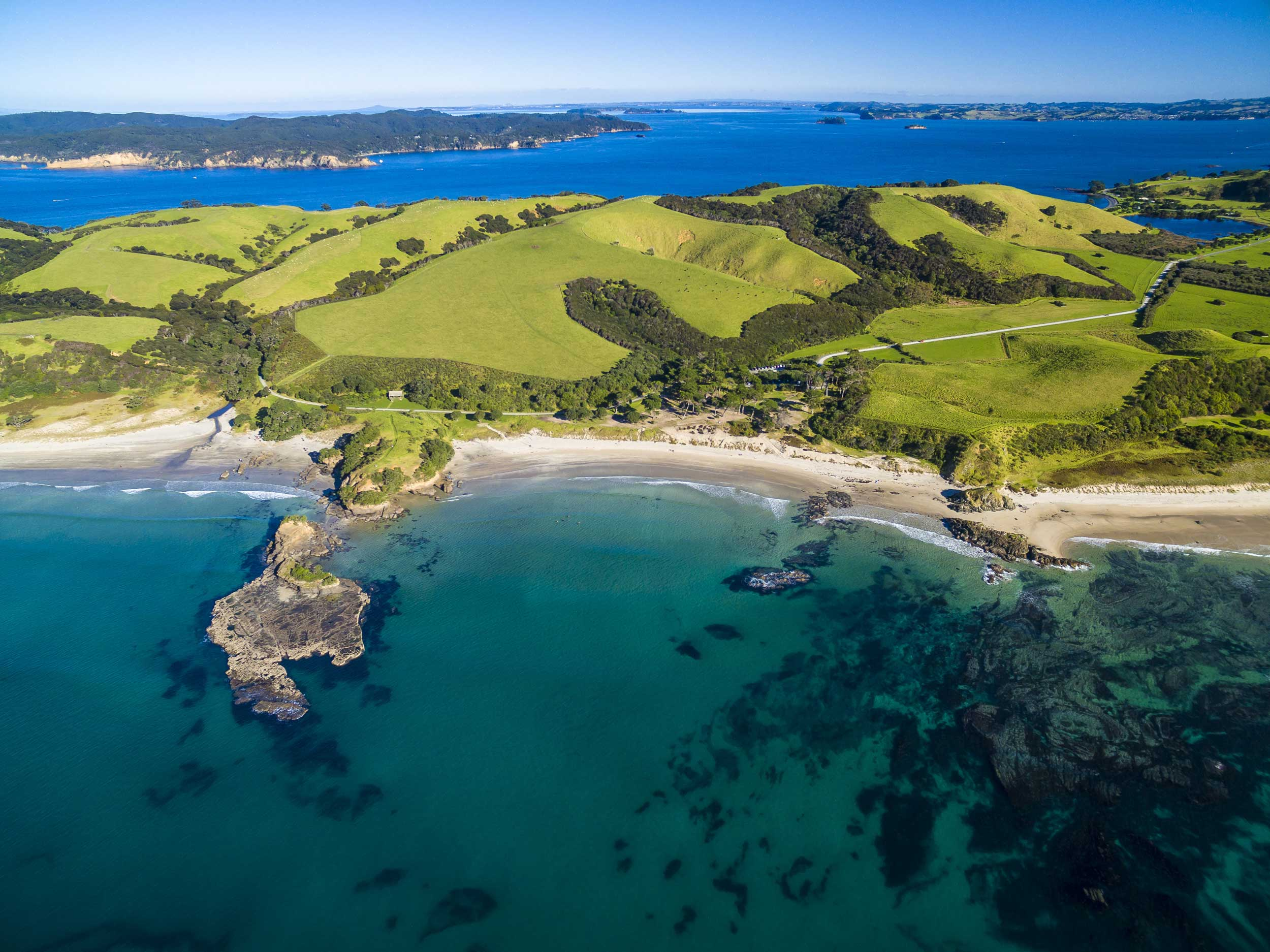 Aerial view of a peninsula with pristine beaches and green hillsides, Auckland