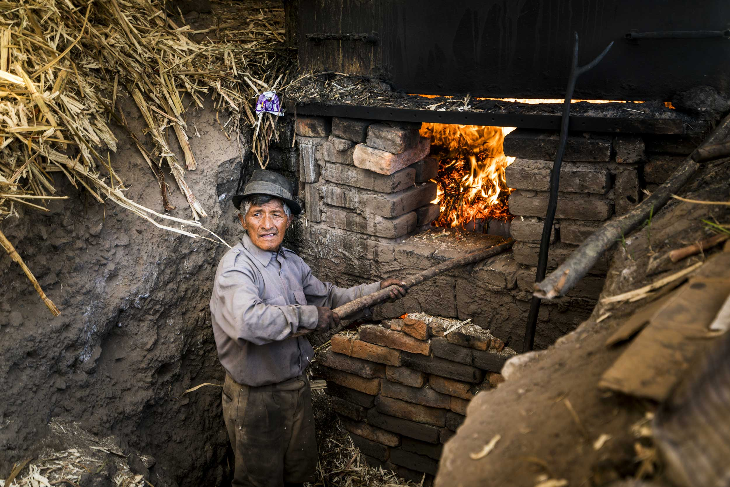 Man tending to fire in a trapiche, Ecuador