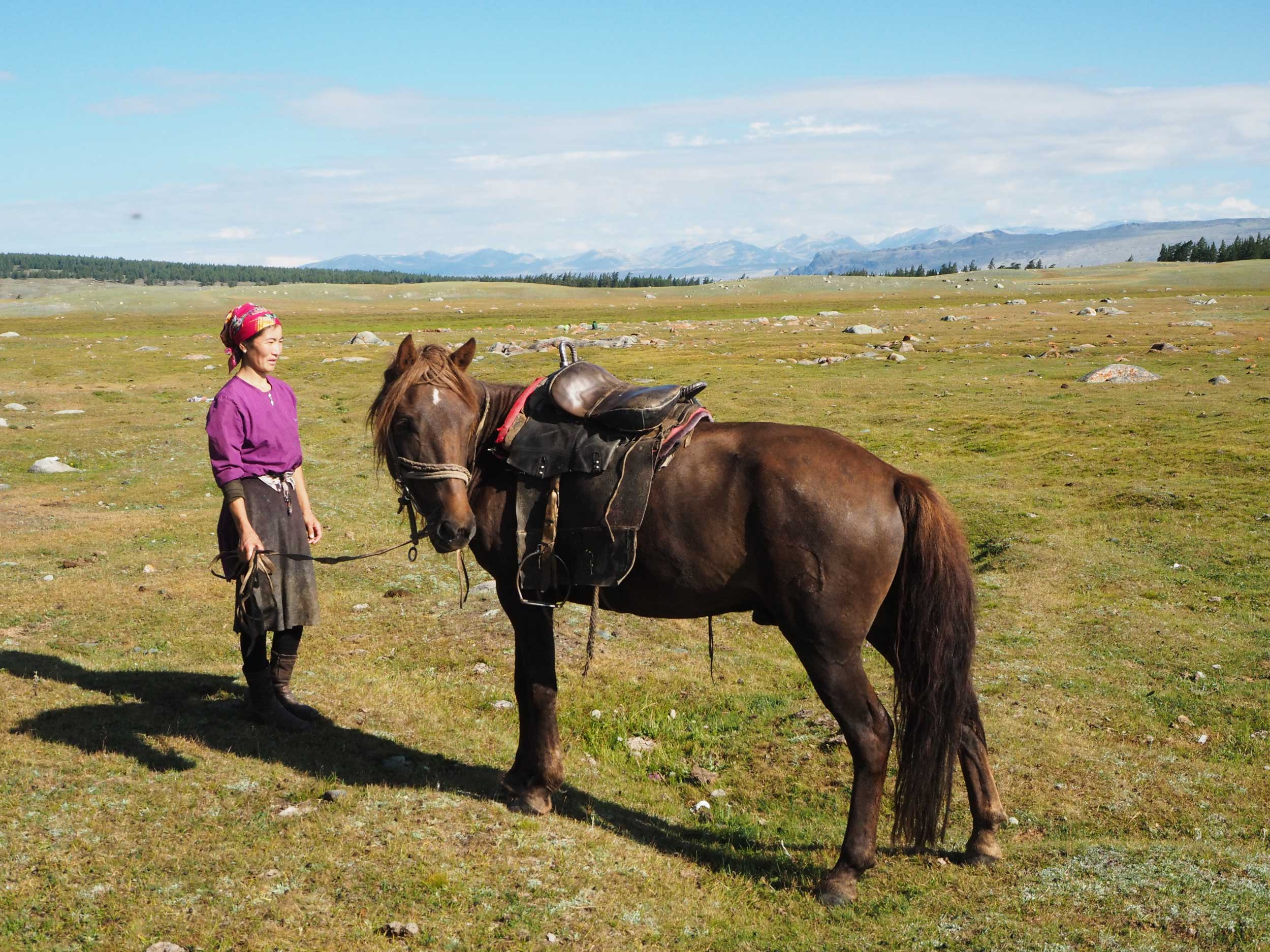 Mongolian woman and a brown horse, Mongolia
