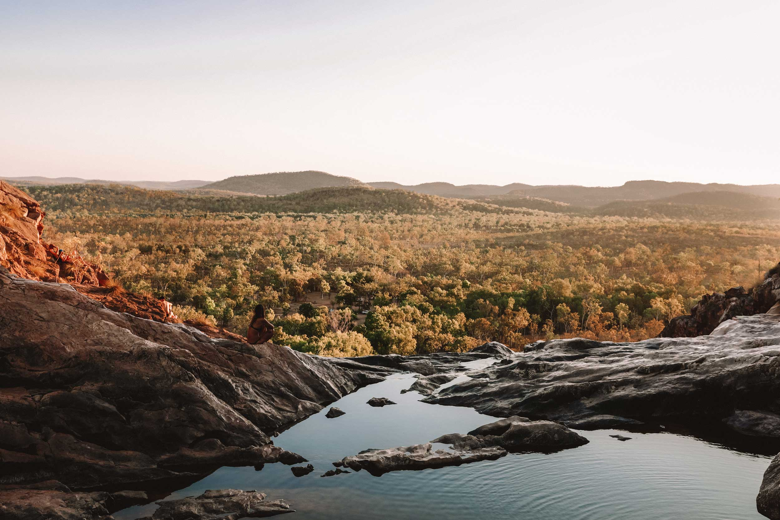 Woman sitting at edge of rock pool above the landscape, Australia