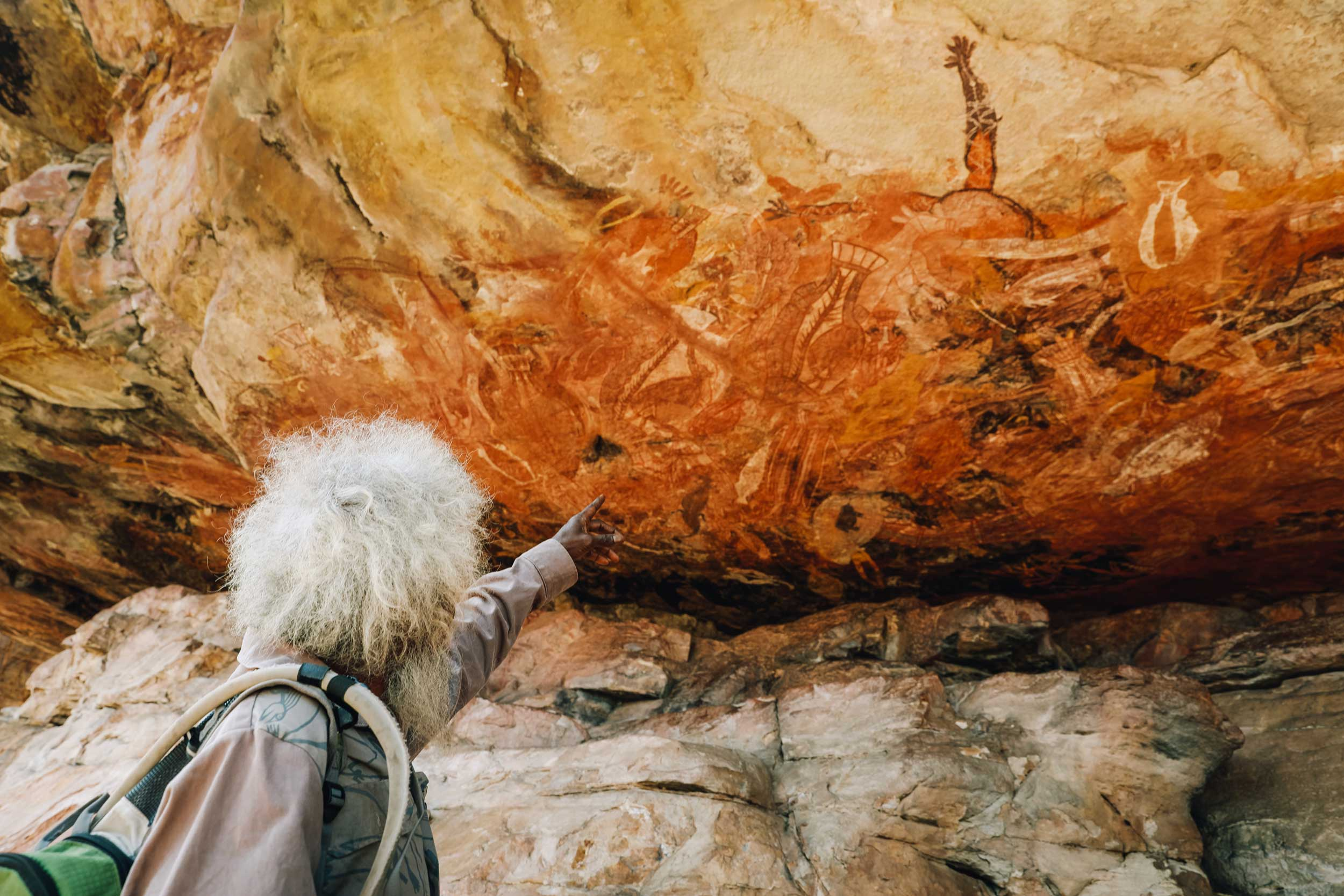 white haired man pointing out Aboriginal art painted an overhanging rock, Injalak, Australia