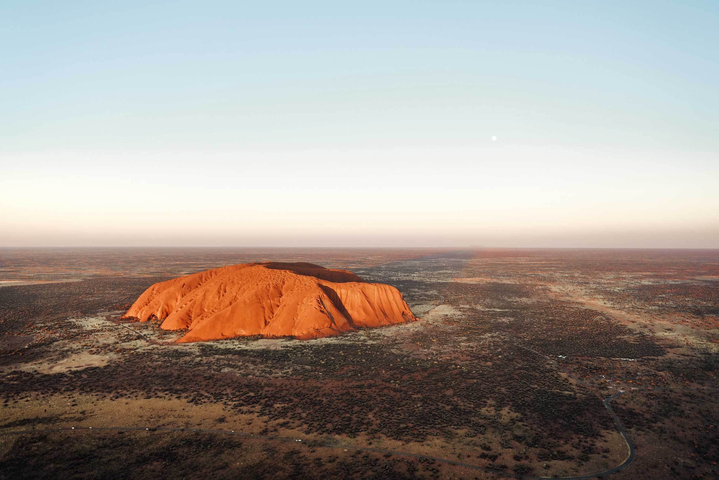Glowing orange, immense rock in the desert, Northern Territory, Australia
